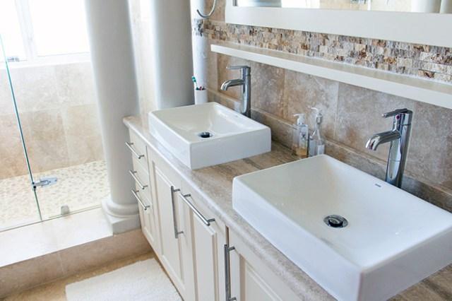 brown bathroom with twin wooden bathroom vanities