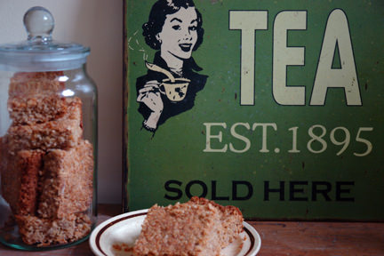 Glass jar full of flapjack pieces, plate with two flapjack pieces and green painted tin retro tea enamel advertising sign | H is for Home