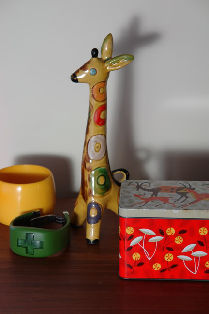 Vintage tin decorated with deer, pottery giraffe from the USSR, wide 60s yellow bangle & green Philippe Stark watch | H is for Home