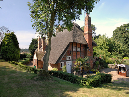 Red brick thatched cottage available to book via Sykes Cottages