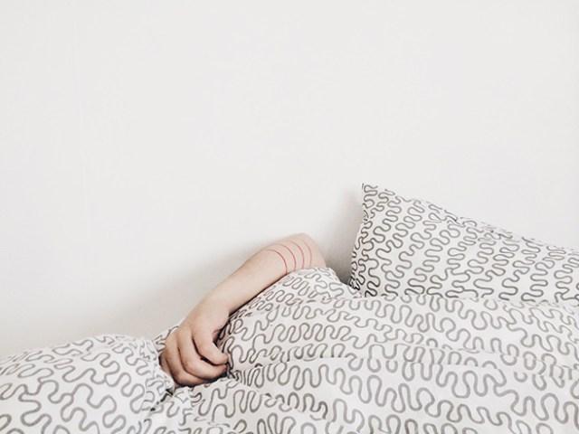 Arm showing above a duvet