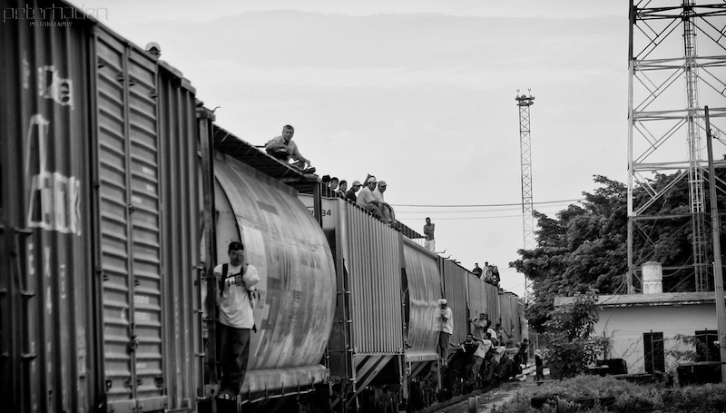 a train rides away with immigrants hanging off the sides.
