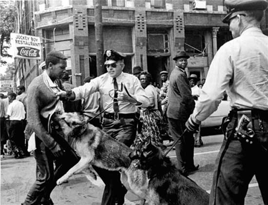 "Hudson, Bill. ""Walter Gadsden of Ullman High School Attacked by Police Dogs at the Birmingham Children's March."" Digital Image. May 3, 1963. Encyclopedia Britannica via the Associated Press. https://www.britannica.com/event/American-civil-rights-movement/Montgomery-bus-boycott-to-the-Voting-Rights-Act."