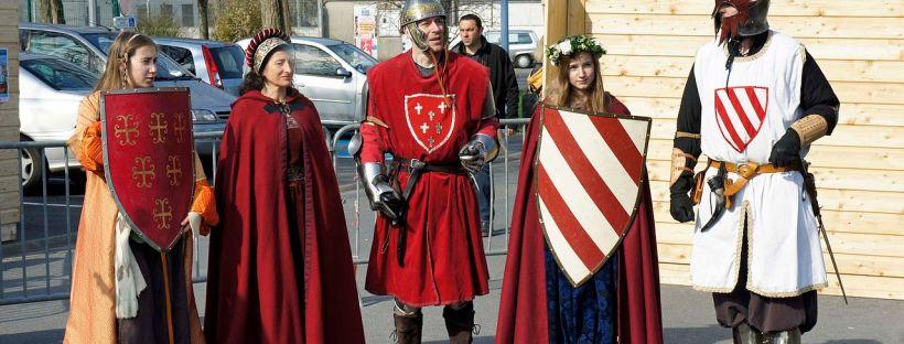 photo d'hommes et de femmes en costumes médiévaux dans une rue aujourd'hui
