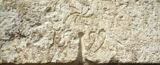 Linteau de porte, rue du pied du village, portant un symbole solaire et le millésime 1599