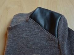De schouderpas, naad naar onderen gestreken en doorgestikt op de jersey.