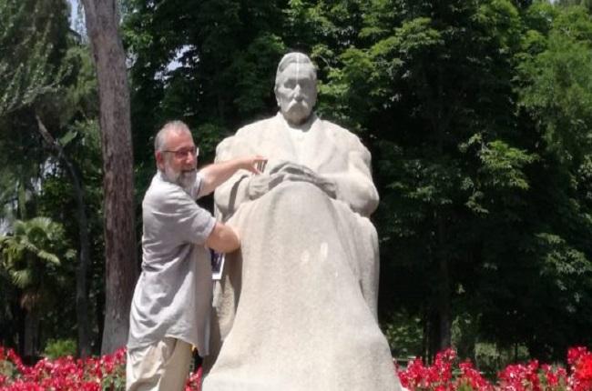 El autor Eduardo Valero junto a una estatua de Benito Peréz Galdós presente en el parque del Retiro, en Madrid