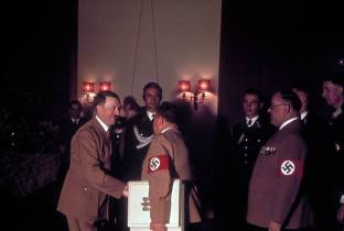 Adolf Hitler shakes hands with one of his personal photographers, Heinrich Hoffmann, while his doctor, Theodor Morrell (right) waits to greet the Fuhrer on Hitler's 50th birthday, April 20, 1939, in Berlin.