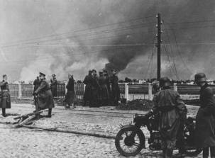 German troops watch Warsaw burn during the attack on the Polish capital city, 1939.