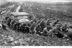 Soldiers pull a staff car through the heavy mud of the Russian roads, November 1941.