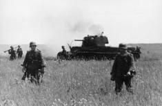 German infantry pass a knocked out Soviet KV-1 heavy tank.