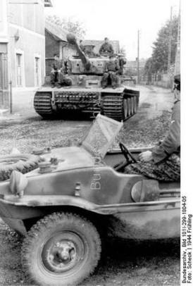 """Tiger I """"(tower number 133) of the first SS-Panzer-Korps """"Leibstandarte Adolf Hitler"""" in town before business """"Nieuverburg"""" in the foreground floating bucket, PK 698 during the Normandy invasion."""