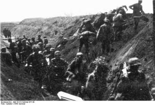 German soldiers move along an anti-tank ditch, while pioneers prepare charges to breach it.