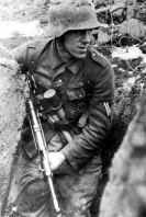 Soldat sneaking down a narrow trench. He is armed with submachine gun MP-40 and M-24 grenades. The Eastern Front, Spring 1944.