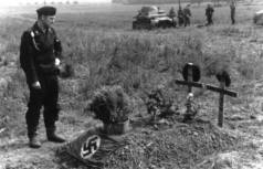 German tank crewman at the grave of his two comrades from PzKpfw IB light tank, which is visible in the background photo.