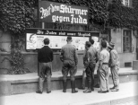 """A group of men read a propaganda billboard titled """"The Jews Are Our Misfortune"""", 1933."""