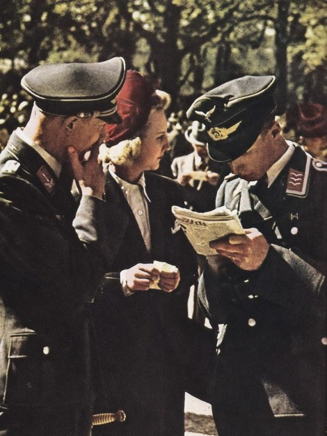 Accompanied by a smartly dressed friend, Luftwaffe officers study the odds at the Auteuil race track (Paris), where underfed horses ran during the Occupation.