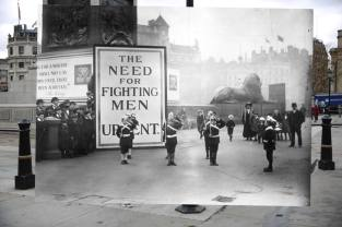 "In the first image, people stand at Trafalgar Square, London, on March 17, 2014. In the second image, London street urchins dressed as soldiers with paper hats and canes as guns stand in Trafalgar Square in 1919. Behind them is a notice declaring ""The Need for Fighting Men is Urgent."""
