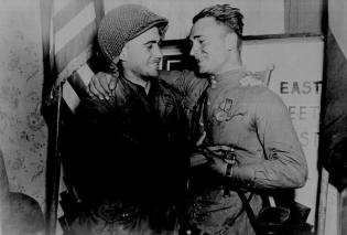 2nd Lt. William Robertson, US Army and Lt. Alexander Sylvashko, Red Army, shown in front of sign East Meets West symbolizing the historic meeting of the Soviet and American Armies, near Torgau, Germany.