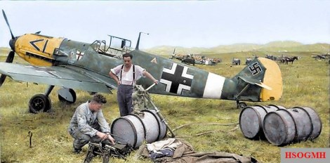 Ground operations around a Messerschmitt Bf 109E-7 of the Luftwaffe's Jagdgeschwader 27 (JG27) possibly during it's brief operational spell in Gela, Sicily between the 3rd and 24th of May 1941. During its stay in Sicily, III./JG27 operated over Malta. The 109 has still got the original JG27's emblem used prior to the move to North Africa. The 109s in the background seem to have a North African camouflage. This is the first time we've seen the rank markings displayed on the nose instead of close to (before or after) the fuselage's Balkenkreuz. In this case the rank seems to be that of a Geschwader Adjutant (Wing Second-in-Command). The markings on the engine cowling are characteristic of III./JG27 and were inherited from the Gruppe's predecessor, I./JG1.