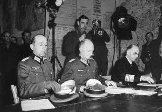 """Jodl, wearing Iron Cross low on his left breast, is seated between the major and admiral. With [German Head of State Karl] Donitz's authorization, he has nothing to do but sign the surrender."""