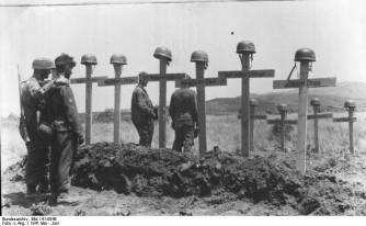 German soldiers pause before the graves of their fallen comrades.