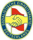 SED logotype: The Communist–Social Democrat handshake of Wilhelm Pieck and Otto Grotewohl, establishing the SED in 1946.