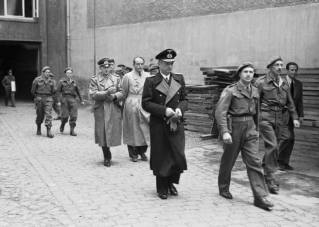 Leading members of the Flensburg Government after their arrest. Karl Dönitz (centre, in long, dark coat) is followed by Speer (bareheaded) and Alfred Jodl (to the left of Speer).