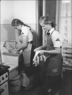 Members of the League of German Girls at work cleaning in a Berlin tenement house, date unspecified.