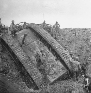 American GIs inspect an overturned German panzer, after it toppled into a crater made by a bomb dropped right in front of it by an Allied plane, December 1944.