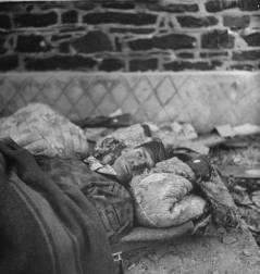 A wounded German soldier rests on makeshift bedding after being taken prisoner during an attack on an American fuel depot on Dec. 16, 1944, the first day of the Battle of the Bulge.