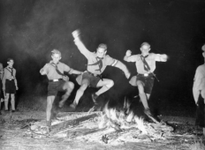 Boys ceremonially jump over a fire as part of a traditional summer solstice festival in Berlin, 1937.