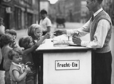 Children buy a frozen dessert from a street vendor in Berlin, 1934.