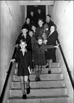 Children and their parents walk down into an air shelter in Berlin, October 1941.