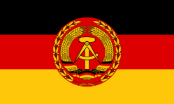 State flag (Staatsflagge) 1959–1990 Merchant flag (Handelsflagge) 1973–1990 Tricolour of black, red, and yellow (same as West German colours), but bears the coat of arms of East Germany, consisting of a compass and a hammer encircled with rye.