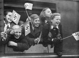 Children wave flags before leaving Berlin, circa 1940-1945. These children are being evacuated from the city to live in Kinderlandverschickung camps, where they will be safe from air raids. Many will be separated from their families.