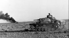 Afrika Korps Pz Mk III advances past a vehicle burning in the desert, April 1941.