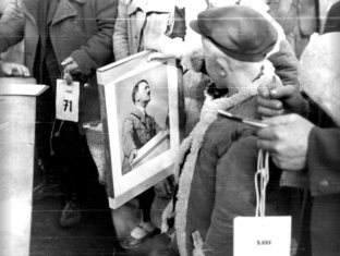 People at a resettlement camp in Lublin, Poland receive framed photos of Adolf Hitler to hang in their apartments, 1940.