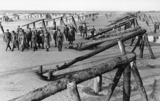 Rommel and local officers inspect defensive preparations on the beaches of Northern France.