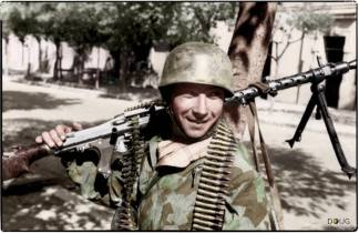 A Fallschirmjäger (Paratrooper) carrying a Maschinengewehr (MG) 34 in Italy, September 1943.