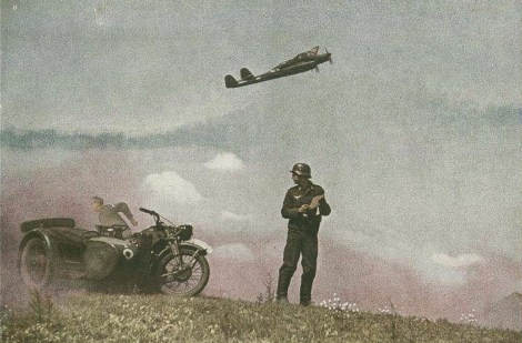 """This photo, which looks prepared, is probably made for the german war propaganda. A Luftwaffe motorcyclist in front of Zündapp Ks 600 with sidecar reads a letter from home as a Focke-Wulf Fw 189 Uhu (""""Eagle Owl"""") roars into the skies."""