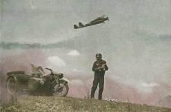 "This photo, which looks prepared, is probably made for the german war propaganda. A Luftwaffe motorcyclist in front of Zündapp Ks 600 with sidecar reads a letter from home as a Focke-Wulf Fw 189 Uhu (""Eagle Owl"") roars into the skies."