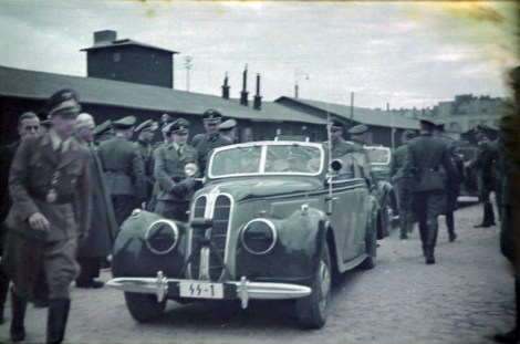 """An official visit of Heinrich Himmler in BMW 355 at the Łódź Ghetto, Thursday, 5 June 1941. The grey-haired man is Mordechai Chaim Rumkowski. He was the """"leader"""" of the Jewish community in the Lodz Ghetto (Litzmannstadt). There were a number of manufacturing enterprises in the ghetto. The German Wehrmacht had orders filled for uniform pieces and other things made by Jewish laborers. Himmler paid a brief visit to the ghetto in connection with the production taking place there. Visible also Himmler's Chief Adjudant Karl Wolff; the man with his face peeking over the shoulder of the Political officer at the far left of the frame is Ghetto Administrator, Hans Biebow; and the man next to the driver could be Dr. Wilhelm Albert."""