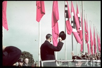 British Prime Minister Neville Chamberlain waves to spectators from an open-top car, shortly after leaving Oberwiesenfeld airport on the way to a meeting with Adolf Hitler over the latter's threats to invade Czechoslovakia, Münich, Germany, 28 September 1938.