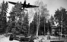 Lent's Bf 110C ran out of fuel and was forced to land at Oslo/Fornebu airfield on 9 April 1940. A troop-carrying Ju 52 flies over Lent's belly-landed Bf 110.