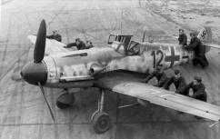 """Luftwaffe ground-crew (""""black men"""") positioning a Bf 109 G-6 """"Kanonenvogel"""" equipped with the Rüstsatz VI underwing gondola cannon kit. Note the slats on the leading edge of the port wing. JG 2, France, late 1943."""
