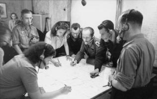 Radio control center for night fighters, Jägerleitoffiziere and assistants plotting courses and directing the airborne fighters.