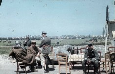 On the outskirts of Dunkirk, a German officer interrogates two captured French officers who sit under guard near a roadside table laden with wine bottles. A German inflatable rubber dinghy is visible behind the table.
