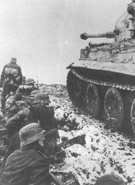 German soldiers take cover beside a Tiger from the 502nd Heavy Tank Battalion near Narva, February 1944.