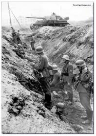 German soldiers wait in a Soviet dug trench and wait for orders to attack.
